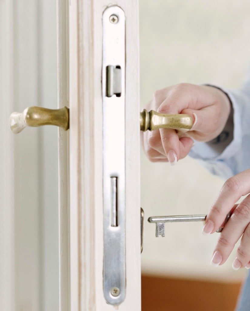 Woman's hand opening door with key