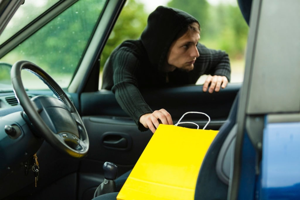 Transportation, crime and ownership concept - thief stealing present from the car during holiday season